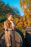 Thoughtful woman standing near wooden barrel Royalty Free Stock Photo