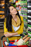 Thoughtful woman standing with shopping cart in grocery section Royalty Free Stock Images