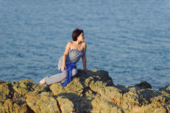 Thoughtful Woman on Stone Royalty Free Stock Photography