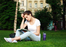 Thoughtful woman student in a city park reading a book Royalty Free Stock Photo