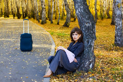 Thoughtful woman with suitcase. Royalty Free Stock Photo