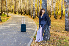 Thoughtful woman with suitcase. Royalty Free Stock Image