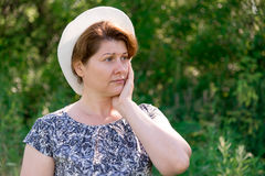 Thoughtful Woman in summer hat on nature Stock Photo
