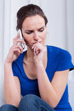 Thoughtful woman talking on the phone Royalty Free Stock Photos