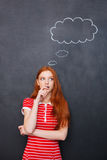 Thoughtful woman thinking over blackboard background with blank bubble Royalty Free Stock Images