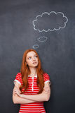 Thoughtful woman thinking over blackboard background with empty speech bubble Stock Photography