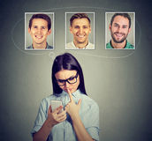 Thoughtful woman thinking which man she likes the most using smartphone app. Thoughtful young women thinking which men she likes loves the most using smartphone Royalty Free Stock Photos