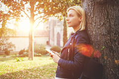 Thoughtful woman tourist is holding smart phone, while is enjoying free time in vacation Royalty Free Stock Images