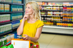 Thoughtful woman with trolley Stock Image