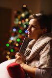 Thoughtful woman with tv remote control near christmas tree Royalty Free Stock Image