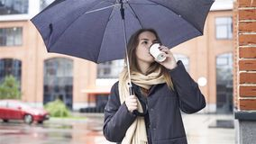 Thoughtful woman under umbrella drinking coffee. Thoughtful attractive young woman wearing a gray coat is standing under an umbrella and drinking coffee stock video