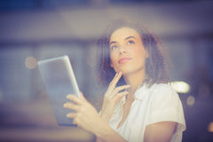Thoughtful woman using a digital tablet Stock Images