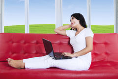 Thoughtful woman using laptop at home. Beautiful young female is working on laptop while sitting on red sofa Royalty Free Stock Image