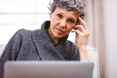 Thoughtful woman using laptop at home Stock Photo