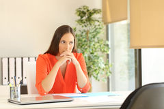 Thoughtful woman waiting for a job interview. Thoughtful and nervous woman waiting for the interviewer during a job interview in a desk at office stock photo