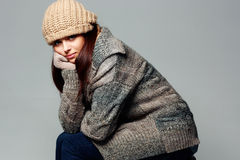 Thoughtful woman in warm winter outfit on gray background Stock Image