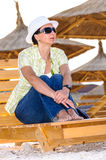 Thoughtful woman on wooden lounge chair Royalty Free Stock Photo
