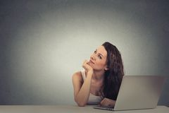 Thoughtful woman working on a laptop thinking looking up Royalty Free Stock Image