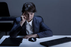 Thoughtful woman working overtime Stock Photography