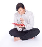 Thoughtful woman writing on clipboard Stock Images