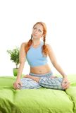 Thoughtful woman in yoga pose. With red hair sitting in bed Royalty Free Stock Images