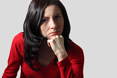 Thoughtful woman. Young brunette with long hair sitting supporting her head with hand looking depressed Stock Images