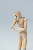 Thoughtful wooden figurine pretending to lean royalty free stock image