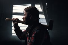 Thoughtful woodsman with axe focus on foreground. Pensive lumberjack in dark room, hard craftsmanship work, male strength background Royalty Free Stock Photos