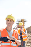 Thoughtful worker standing at construction site with colleague in background Royalty Free Stock Photo
