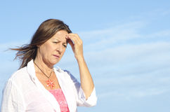 Thoughtful worried senior woman isolated. Worried and concerned looking senior woman outdoor, isolated with blue sky as background and copy space royalty free stock photos