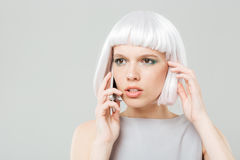Thoughtful worried woman in blonde wig talking on mobile phone Royalty Free Stock Photography