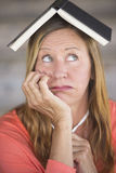 Thoughtful worried woman with book on head Stock Image