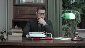 Thoughtful writer sitting in front of typewriter waiting for inspiration for his new book stock footage