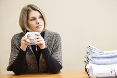 Thoughtful yong woman drinking coffee, blueprints at table Stock Images