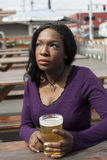 Thoughtful Young African American Woman Drinks Pint of Pale Ale Stock Images