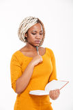 Thoughtful young african american woman thinking and writing in notebook Royalty Free Stock Images