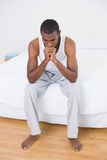 Thoughtful young Afro man sitting on bed Stock Photo