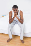 Thoughtful young Afro man sitting on bed Royalty Free Stock Photos