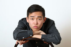 Thoughtful young Asian man looking at camera Stock Images