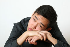Thoughtful young Asian man looking at camera Royalty Free Stock Photo