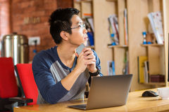 Thoughtful young asian man using laptop in cafe Royalty Free Stock Photo