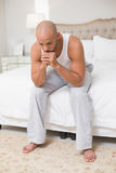 Thoughtful young bald man sitting on bed Royalty Free Stock Photo