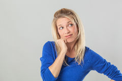 Thoughtful young blond woman daydreaming, looking away from mistake Stock Image