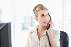 Thoughtful young blonde businesswoman answering the telephone. At office Royalty Free Stock Images
