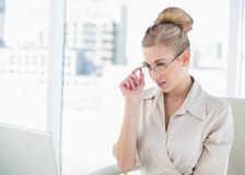 Thoughtful young blonde businesswoman looking over her glasses Royalty Free Stock Photos