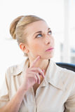 Thoughtful young blonde businesswoman looking up. At office Royalty Free Stock Image