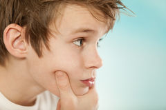 Thoughtful young boy grasping his chin. Close up on the face of a handsome thoughtful young boy grasping his chin and looking towards blue copyspace, profile Royalty Free Stock Photography