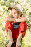 Thoughtful young boy staring at the camera. Thoughtful barefoot young boy in a floppy sunhat sitting on a plank of wood resting his chin on his arms staring at Stock Photos