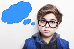 Thoughtful boy wearing glasses with an empty thought bubble. Thoughtful young boy wearing glasses with an empty thought bubble Stock Photos