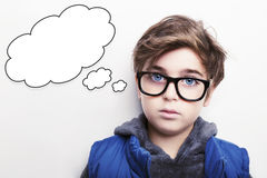 Thoughtful young boy wearing glasses with an empty thought bubble. Thoughtful  boy wearing glasses with an empty thought bubble Royalty Free Stock Images